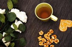 En kopp av grönt te på en tabell med vita blommor och en valnöt på en mörk bakgrund royaltyfria foton