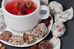 En kopp av jordgubbete och halvor av klippta godisar royaltyfria bilder