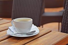 En kopp av kaffe på en trätabell Arkivbild