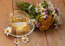 En kopp av kamomillte i en glass kopp och en bukett av fältsommar blommar på en träyttersida Royaltyfri Foto