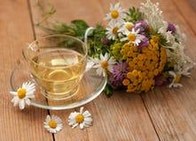 En kopp av kamomillte i en glass kopp och en bukett av fältsommar blommar på en träyttersida Royaltyfria Foton