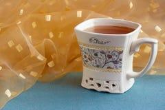 En kopp av läckert smaksatt te är på tabellen royaltyfria bilder