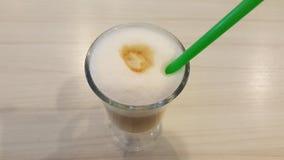 En kopp av latte på en tabell Fotografering för Bildbyråer