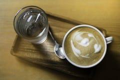 En kopp av Lattekaffe tjänades som samman med ett exponeringsglas av vatten som sätter på trämagasinet royaltyfri bild