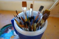 En kopp av målarfärgborstar Arkivbilder