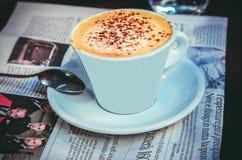 En kopp av nytt bryggad cappuccino på tabellen med tidningen royaltyfri foto