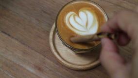 En kopp av pickolaflöjtlattekaffe med lattekonst stock video