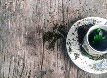 En kopp av plattor för grönt te och vit, och torkade våta teblad för teblad och på träbakgrund Royaltyfri Foto