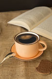 En kopp av smileykaffe med en bok Arkivfoto