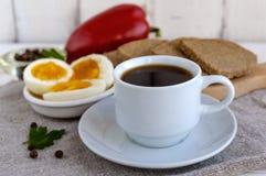 En kopp av starkt kaffe & x28; espresso& x29; , bantar närbilden och lätta frukosten - kokt ägg- och rågbröd Royaltyfri Bild