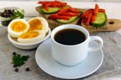 En kopp av starkt kaffe & x28; espresso& x29; , bantar närbilden och lätta frukosten - kokt ägg- och rågbröd Arkivfoto