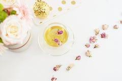 En kopp av sund örtte med torkade rosor Härliga nya blommor, guld- ananas, anteckningsbok på den ljusa marmortabellen, bästa sikt Arkivbilder