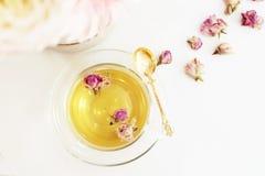 En kopp av sund örtte med torkade rosor Härliga nya blommor på den ljusa marmortabellen, bästa sikt Rosa bukett på en kvinnlig wo Arkivbilder