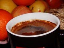 En kopp av svart kaffe för morgon med frukter i bakgrunden royaltyfri fotografi