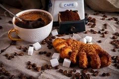 En kopp av svart kaffe med en bulle, kaffebönor och stycken av socker spridda på en tabell som täckas med säckväv royaltyfria foton