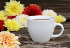 En kopp av svart kaffe och dahlior färgar blomman på tabellen suddighet bakgrund Arkivfoto