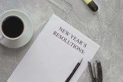 En kopp av svart kaffe och en upplösning för ` s för nytt år skyler över brister med brevpapper Arkivfoto