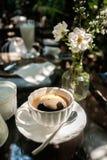 En kopp av svart kaffe som förläggas på den glass tabellen Arkivfoton