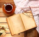 En kopp av svart te med tappningboken Arkivbild