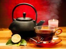 En kopp av svart te med tekannan i bakgrunden Royaltyfria Bilder