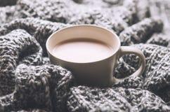 En kopp av varm kakao med mjölkar på den grå ull stack plädet Hem- cosiness Top beskådar royaltyfri foto