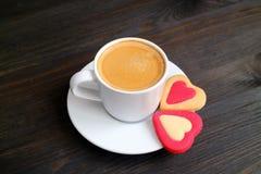 En kopp av varmt kaffe med ett par av hjärta formade kakor på trätabellen för mörk färg arkivfoton