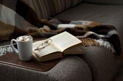 En kopp av varmt kaffe med marmeladboken pekar filten på soffan Royaltyfria Foton