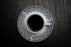 En kopp av varmt kaffeanseende på trätabellen Skådespelare - två apelsiner Fotografering för Bildbyråer