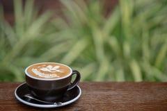 En kopp av varmt lattekonstkaffe på den wood tabellen royaltyfria foton