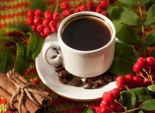 En kopp av varmt starkt kaffe, kanelbruna pinnar, mogna askabär och kaffebönor på en stucken yttersida Arkivbild