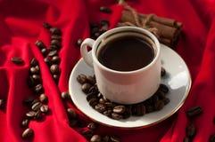 En kopp av varmt starkt kaffe, kanelbruna pinnar och kaffebönor på ett rött draperat tyg Royaltyfria Bilder