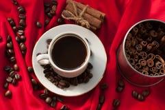 En kopp av varmt starkt kaffe, kanelbruna pinnar och kaffebönor på ett rött draperat tyg Fotografering för Bildbyråer