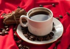 En kopp av varmt starkt kaffe, kanelbruna pinnar och kaffebönor på ett rött draperat tyg Royaltyfri Fotografi