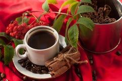 En kopp av varmt starkt kaffe, kanelbruna pinnar och kaffebönor på ett rött draperat tyg Arkivbild