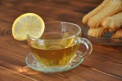 En kopp av varmt te med citronen och bakelse royaltyfri bild