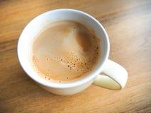 En kopp av vitt kaffe på den bruna tabellen Royaltyfri Foto
