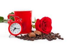 En kopp, en klocka och röd ros Arkivbilder
