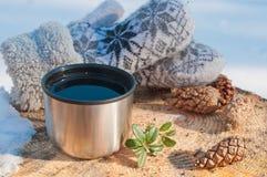 En kopp från en termos med te på en stubbe i en skog Arkivfoton