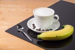 En kopp kaffe i en vit kopp med bananen och skeden på trä och svart tavlabakgrund Royaltyfria Foton