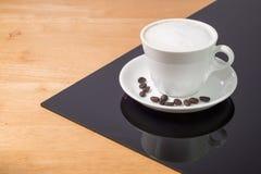 En kopp kaffe i en vit kopp och sked på trä och svart tavlabakgrund arkivfoto
