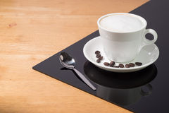 En kopp kaffe i en vit kopp och sked på trä och svart tavlabakgrund royaltyfria bilder
