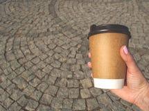 En kopp kaffe i en hand för kvinna` s arkivfoton