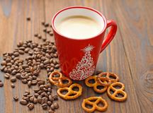 En kopp kaffe, korn av kaffe och kakor på en trätabell arkivbilder