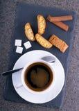 En kopp kaffe med cantuccini på en kritiseraplatta Arkivbild
