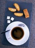 En kopp kaffe med cantuccini på en kritiseraplatta Arkivfoton