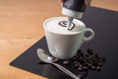 En kopp kaffe med danandemodellen i en vit kopp och sked på trä och svart tavlabakgrund royaltyfri bild
