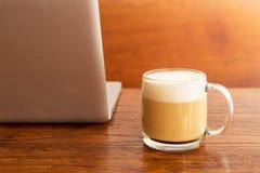 En kopp kaffe med datoranteckningsboken Arkivfoton
