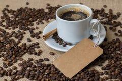 En kopp kaffe med den kaffebönor och etiketten Fotografering för Bildbyråer