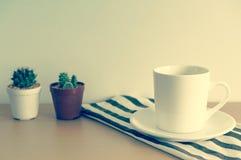 En kopp kaffe med den lilla kaktuns på trätabellen, tappningstil Royaltyfri Bild