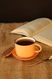 En kopp kaffe med en bok Arkivbild